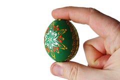 Det gröna easter ägget, hand blowed och målade, rymt i hand av den vuxna manliga personen, vit bakgrund arkivfoton