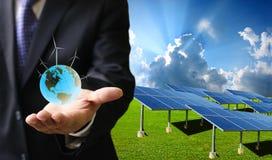 Det gröna energibegreppet, affärsman bär världen av vindturbinen royaltyfri foto