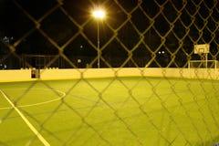 Det gröna fotbollfältet tände vid lyktor i aftonen i sommaren Fotografering för Bildbyråer