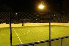Det gröna fotbollfältet tände vid lyktor i aftonen i sommaren Arkivfoto