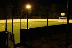 Det gröna fotbollfältet tände vid lyktor i aftonen i sommaren Arkivbilder