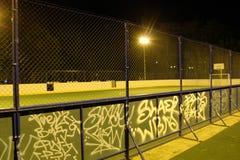 Det gröna fotbollfältet tände vid lyktor i aftonen i sommaren Royaltyfri Foto