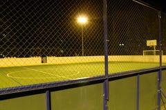Det gröna fotbollfältet tände vid lyktor i aftonen i sommaren Arkivbild