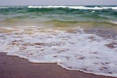 Det gröna havet vinkar på stranden Royaltyfria Bilder