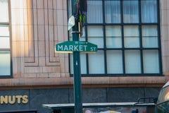 Det gröna Market Street tecknet på en grön pol med ett stort mång--förser med rutor fönstret på en gammal kontorsbyggnad i bakgru royaltyfri foto
