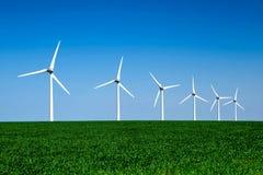 Det grafiska moderna landskapet av vindturbiner arrangera i rak linje i ett fält Arkivfoto