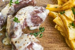 Det grillade kalvköttet med fransmansmåfiskar tjänade som med sås på den glass plattan för closeupeyedroppers hög för upplösning  arkivfoton