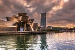 Det Guggenheim museet Bilbao och Iberdrola torn på den dramatiska solnedgången arkivbilder