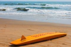 Det gula br?det av r?ddaren f?r att surfa ligger p? sanden som anv?nds av livr?ddaren som arbetar p? den Arambol stranden arkivfoton
