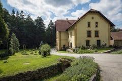 Det gula huset med pelargon i mitt av en gräsplan parkerar Royaltyfria Foton