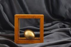 Det guld- ägget betonade vid placering i den wood ramen Arkivfoto