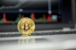 Det guld- bitcoinmyntet på ett silvertangentbord av bärbara datorn och diagrammet kartlägger grafen på en skärm som en bakgrund f arkivbild