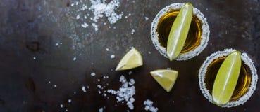Det guld- mexikanska tequilaskottet med grön limefrukt och saltar fotografering för bildbyråer