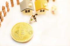 Det guld- myntet för det Bitcoin cryptocurrencytecknet kommer med lyckligt finansiellt frihetsliv till miniatyrparfolk Investerin royaltyfria foton