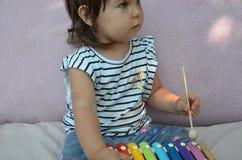 Det gulliga barnet behandla som ett barn flickalilla barnet som spelar med den hemmastadda xylofonen Kreativitet- och utbildnings arkivfoto