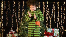 Det gulliga barnet dansar spännande framme av julgranen arkivfilmer