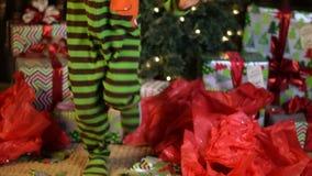 Det gulliga barnet dansar spännande framme av julgranen stock video