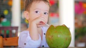 Det gulliga barnet dricker en kokosnötho ett sugrör, närbild Begrepp: Barn lycklig barndom, sommar, behandla som ett barn, semest arkivfilmer