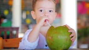 Det gulliga barnet dricker en kokosn?tho ett sugr?r, n?rbild Begrepp: Barn lycklig barndom, sommar, behandla som ett barn, semest stock video