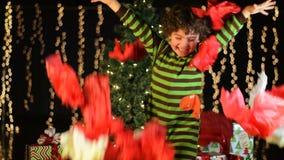 Det gulliga barnet kastar julinpackningspapper i luften lager videofilmer