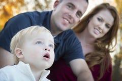 Det gulliga barnet ser upp till skyen, som unga föräldrar ler Royaltyfri Fotografi