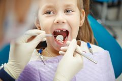 Det gulliga barnet sitter på tandläkarestol med leende royaltyfri fotografi