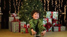 Det gulliga barnet sitter spännande framme av julgranen arkivfilmer