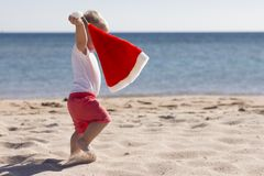 Det gulliga barnet som firar jul och nytt år, semestrar i den karibiska stranden som kläs som jultomten arkivbild