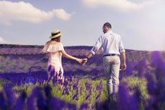 Det gulliga barnparet som är förälskat i ett fält av lavendel, blommar Tyck om ett ögonblick av lycka och förälskelse i ett laven royaltyfri bild