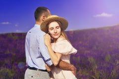 Det gulliga barnparet som är förälskat i ett fält av lavendel, blommar Tyck om ett ögonblick av lycka och förälskelse i ett laven royaltyfria foton
