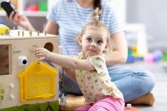 Det gulliga lilla barnet behandla som ett barn att spela med busyboard Bildande leksaker för barn` s arkivbilder