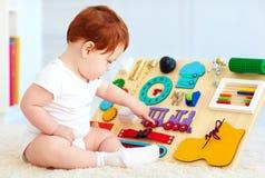 Det gulliga lilla barnet behandla som ett barn att spela med det hemmastadda upptagna brädet Royaltyfri Bild