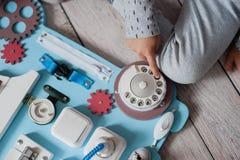 Det gulliga lilla barnet behandla som ett barn att spela med det hemmastadda upptagna brädet Arkivfoton