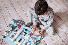 Det gulliga lilla barnet behandla som ett barn att spela med det hemmastadda upptagna brädet Royaltyfri Fotografi