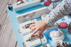 Det gulliga lilla barnet behandla som ett barn att spela med det hemmastadda upptagna brädet Arkivbild