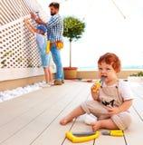 Det gulliga lilla barnet behandla som ett barn hjälpa hans familj med renovering Arkivfoton