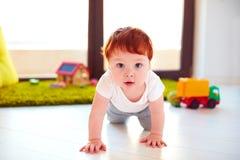 Det gulliga lilla barnet behandla som ett barn krypning på golvet hemma Arkivbild