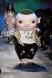 : Det gulliga lilla monstret Wuba och formgivaren Vivienne Tam går landningsbanan Arkivfoto