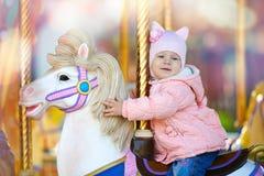Det gulliga lyckliga barnet som rider hästen på det färgrika glat, går rundan Royaltyfri Fotografi