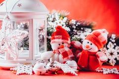 Det gulliga paret av små snögubbear står nära den vita felika lyktan med en leksakhjärta på det och dekorerad granträdfilial Arkivbilder