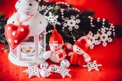 Det gulliga paret av små snögubbear står nära den vita felika lyktan med en leksakhjärta på det och dekorerad granträdfilial Royaltyfria Bilder