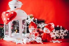 Det gulliga paret av små snögubbear står nära den vita felika lyktan med en leksakhjärta på det och dekorerad granträdfilial Arkivfoto