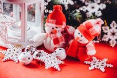 Det gulliga paret av små snögubbear står nära den vita felika lyktan med en leksakhjärta på det och dekorerad granträdfilial Royaltyfri Foto