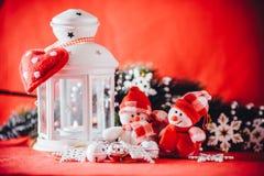 Det gulliga paret av små snögubbear står nära den vita felika lyktan med en leksakhjärta på det och dekorerad granträdfilial Royaltyfri Fotografi