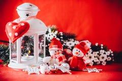 Det gulliga paret av små snögubbear står nära den vita felika lyktan med en leksakhjärta på det och dekorerad granträdfilial Royaltyfri Bild