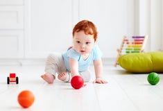 Det gulliga spädbarnet behandla som ett barn krypning på det hemmastadda golvet och att spela med färgrika bollar Arkivbild