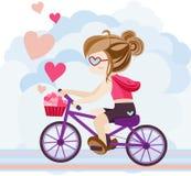 Det gulliga tecknad filmflickateckenet rider en cykel som levererar hjärta Arkivfoto
