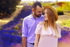 Det gulliga unga lyckliga paret som är förälskat i ett fält av lavendel, blommar Tyck om ett ögonblick av lycka och förälskelse i royaltyfria foton
