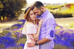 Det gulliga unga lyckliga paret som är förälskat i ett fält av lavendel, blommar Tyck om ett ögonblick av lycka och förälskelse i arkivfoto