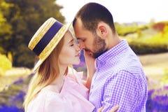 Det gulliga unga lyckliga paret som är förälskat i ett fält av lavendel, blommar Tyck om ett ögonblick av lycka och förälskelse i arkivfoton